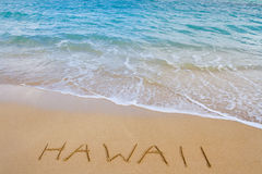 Hawaii Beach and Waves. The word Hawaii is written in the sand of this beach as waves come in to wash it away. This is a vacation image showing the tropical stock photos