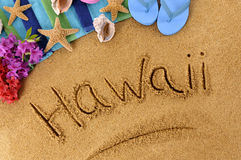 Hawaii beach writing. The word Hawaii written on a sandy beach, with flowers, beach towel, starfish and flip flops Stock Photo