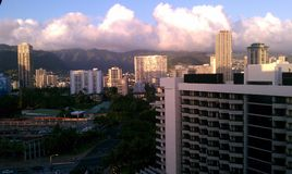 Tropical City Skyline. A sunset view of the City of Honolulu.  The sun casts shadows upon buildings among the backgrounds of mountains and clouds Stock Image