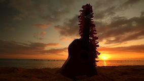 Hawaii concept with ukulele and lei on the beach at sunset. Traditional Hawaiian instrument and flower wreath or garland lei on sandy beach at sunset Oahu Hawaii stock footage
