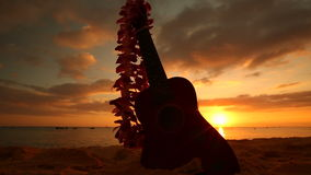 Hawaii concept with ukulele and lei on the beach at sunset stock video
