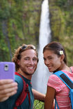 Hawaii couple tourists taking travel phone selfie. Self portrait with camera phone on Hawaii, Big Islands, Akaka Falls. Happy cheerful young multicultural stock photography