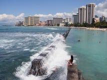 Hawaii Crashing waves. Teenage girls hit by a wave at Waikiki Beach, Honolulu, Hawaii Stock Images