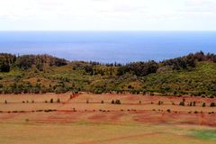 Hawaii Fields. With red dirt in foreground, in background is green trees and foliage and the ocean meets the sky Stock Images