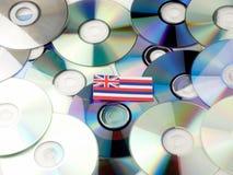 Hawaii flagga överst av CD- och DVD-högen som isoleras på vit Royaltyfria Bilder