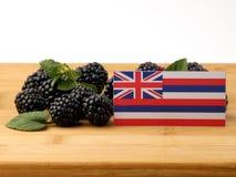 Hawaii flagga på en träpanel med björnbär som isoleras på en wh Royaltyfri Foto