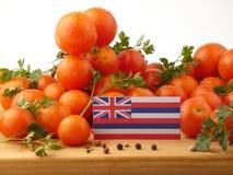 Hawaii flagga på en träpanel med tomater som isoleras på en vit Arkivbilder