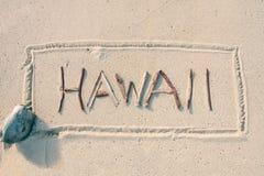 Hawaii geschrieben mit Steuerknüppeln auf den Sand Stockbilder