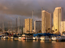 Hawaii harbor sunset. A view of yachts and high rises over the water of a harbor at sunset time in Honolulu (Oahu, Hawaii).  Heavy clouds on the background Royalty Free Stock Photography