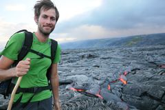 Hawaii hiker hiking by flowing lava. From Kilauea volcano around Hawaii volcanoes national park, USA. Young caucasian man Stock Photo