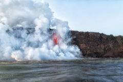 Hawaii Lava flow with vog aka volcanic gases. Red hot lava flows into Pacific Ocean from tube high on the cliffs on The Big Island of Hawaii Stock Image