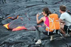 Hawaii lava tourists. Hawaii lava tourist. Tourists taking photo of flowing lava from Kilauea volcano around Hawaii volcanoes national park, USA Royalty Free Stock Images