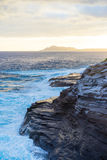 Hawaii Oceanside Cliffs at Sunset. Waves crashed against the cliffs as the sun began to set on Oahu, Hawaii Stock Photos