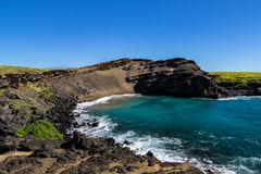Hawaii`s green sand beach. Steep cliff, blue-green water, blue sky. Rocky shoreline in foreground. stock photos