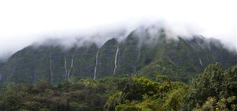 Hawaii Scenery: Rainy Season Mountain Waterfalls. Panorama view of the beautiful scenic tropical waterfalls on the island of Oahu in Hawaii on the misty Koolau Royalty Free Stock Image