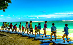 Hawaii Surfing Lesson. Waikiki Beach, , Oahu, Hawaii, USA - September 20, 2015: Asian tourists to Hawaii learn how to stand on their sufboards prior to testing stock photos