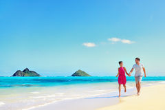 Hawaii vacation couple walking on turquoise beach. Hawaii vacation couple walking relaxing on white sand and pristine turquoise ocean water on Hawaiian beach Royalty Free Stock Photo
