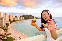 Hawaii vacation - Mai Tai and Aloha spirit woman. Hawaii vacation - Mai Tai and aloha spirit. Asian tourist woman showing Shaka hand sign as welcoming greeting Stock Photo
