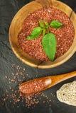 Hawaiiaans rood zout op een houten raad Verkoop van kruiden Reclame voor de verkoop van kruiden Stock Afbeelding