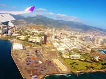 Hawaiian airlines wing of plane above honolulu Stock Photos