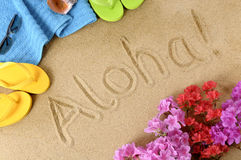 Aloha Hawaii beach. The word Aloha written in soft sand with flip flops, flowers and beach towel Royalty Free Stock Image