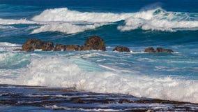 Hawaiian beach with blue waves. Hawaiian beach with blue ocean waves with blue sky and rocky beach stock photo