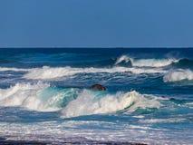Hawaiian beach with blue waves. Hawaiian beach with blue ocean waves with blue sky and rocky shore royalty free stock photos