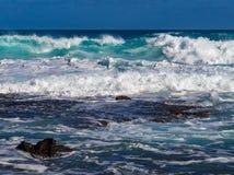 Hawaiian beach with blue waves. Hawaiian beach with blue ocean waves with blue sky and rocky shore stock images