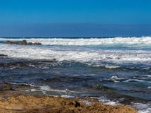 Hawaiian beach with blue waves. Hawaiian beach with blue ocean waves with blue sky and rocky beach royalty free stock photo