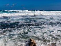 Hawaiian beach with blue waves. Hawaiian beach with blue ocean waves with blue sky and rocky shore stock photo