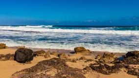 Hawaiian beach with blue waves. Hawaiian beach with blue ocean waves with blue sky and rocky beach royalty free stock images
