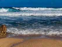 Hawaiian beach with blue waves. Hawaiian beach with blue ocean waves with blue sky and rocky beach stock photography