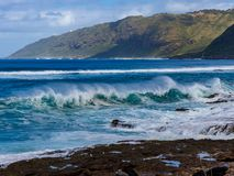 Hawaiian beach with blue waves. Hawaiian beach with blue ocean waves with blue sky and rocky beach royalty free stock photos