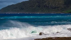 Hawaiian beach with blue waves. Hawaiian beach with blue ocean waves with blue sky and rocky beach stock images