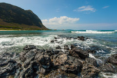 Hawaiian beach with sand and mountain background Stock Photos