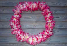 Hawaiian garland of flowers, wreath on a wooden background. Hawaiian beads for wearing on the neck in the form of a garland during a national holiday on wooden stock photography
