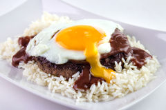 Hawaiian burger. Loco Moco , traditional Hawaiian cuisine , burger patty on rice with a fried egg and brown gravy sauce Royalty Free Stock Photography