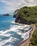 Hawaiian Coastline with a Black Sand Beach. The rugged Hawaiian coastline on the Northern tip of the big island with waves crashing into a black sand beach Stock Photos