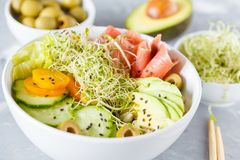 Salmon poke with rice, avocado and sprouts.