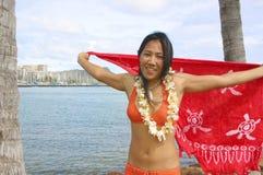 Hawaiian girl in Bikini. Young Hawaiian girl in bikini wearing lei and holding red pareo with turtle pattern. Waikiki in background royalty free stock photos