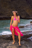 Hawaiian girl with flowers on lava. A hawaiian girl with flowers on lava cliffs by the ocean in Hawaii Royalty Free Stock Image