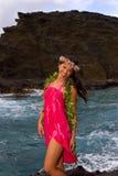 Hawaiian girl with flowers on lava. A hawaiian girl with flowers on lava cliffs by the ocean in Hawaii Royalty Free Stock Photos