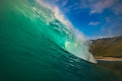Surfing wave green blue barrel in Hawaii. Hawaiian huge shorebreak wave. Ocean water for watersport activity. Surfing lessons at sunset time. Nobody on this Stock Photography