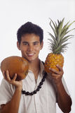 Hawaiian man with cocnut and pineapple. Hawaiian man wearing a kukui nut lei holds a pineapple and a coconut Stock Photography