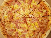 hawaiian pizza, with ham, cheese and pineapple chunks stock photography