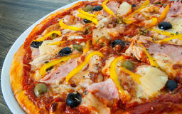 Hawaiian pizza with pineapple, ham, chicken, cheese, olives and vegetables Royalty Free Stock Photos