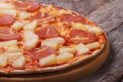 Hawaiian pizza with pineapple and ham on an old wooden table Royalty Free Stock Photo