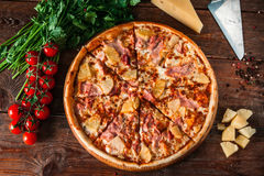 Hawaiian pizza on rustic wood table, flat lay. Appetizing hawaiian pizza with ham, cheese and pineapple, served on rustic wooden background with cherry, tomatoes Royalty Free Stock Photos