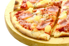 Hawaiian pizza slice on wooden board isolated. Hawaiian pizza with pineapple, ham and cheese on wooden cutting board, studio isolated royalty free stock photography