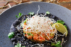 Hawaiian poke on black sesame flat cake. Modern restaurant food background Royalty Free Stock Image